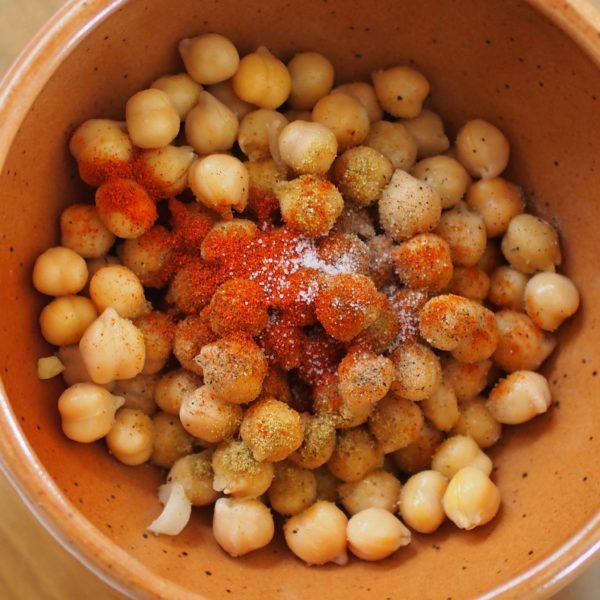 Une fois le pois chiche égoutté mais pas essuyé, ajoutez le mélange d'épices de votre choix. Un mélange cumin, paprika, sel, poivre, ail par exemple.