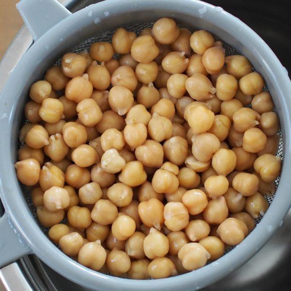Si vous utilisez du pois chiche ou du soja dépelliculé secs faites les tremper la veille dans trois fois leur volume d'eau. Le lendemain, rincez vos légumineuses et faites cuire le soja dépellicullé pendant 40 minutes dans un grand volume d'eau claire. Cette étape est facultative pour le pois chiche mais vous pouvez le cuire une vingtaine de minutes pour améliorer la digestibilité. Enfin, si vous utilisez du pois chiche en conserve rincez le simplement. Une fois la première étape effectuée pour chaque cas, préchauffez votre four à 165° Celsius. Si la température est trop élevée, vos légumineuses risque de brûler à l'extérieur tout en restant molles à l'intérieur.