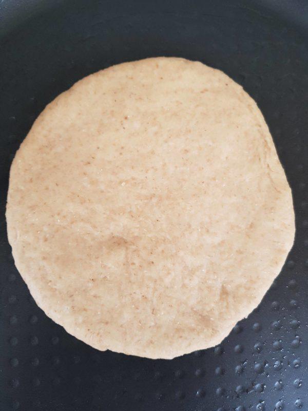 Dégazez votre pâte et faites 4 boules de tailles égales. Étalez les à l'aide d'un rouleau à pâtisserie afin de former des disques épais et homogènes. Si les disques sont trop fins vous ne pourrez pas couper les pains ensuite. Laissez reposer à couvert une quinzaine de minutes pendant lesquelles vous pourrez préchauffer votre poêle préalablement huilée à feu très doux. Vous pouvez prolonger le temps de repos pour avoir un pain encore plus moelleux.