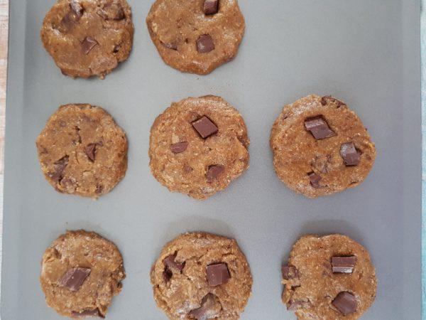Versez le mélange obtenu dans le premier bol et mélangez soigneusement. Si le mélange est trop sec avec la farine choisie, ajoutez les 8g d'eau. Faites 8 cookies avec la pâte obtenue. N'oubliez pas les pépites de chocolat pour la déco extérieure.