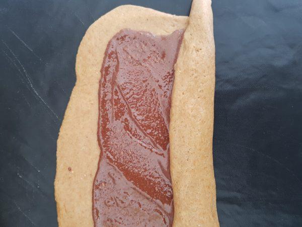Préchauffez votre four à 180°C. Etalez ensuite votre pâte à l'aide d'un rouleau selon la forme d'un rectangle. Elle devrait pouvoir être manipulée sans problème à ce stade. Si ce n'est pas le cas, farinez légèrement votre rouleau. Etalez ensuite votre nappage sur votre pâte en prenant soin de laissez un espace dans le sens de la longueur pour ne pas que le chocolat ne déborde en roulant votre pâte.