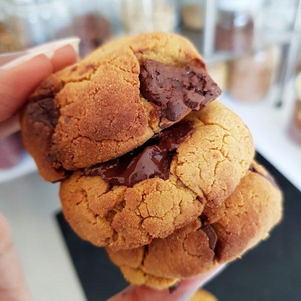 La pâte vous paraîtra assez friable ce qui est normal. Faites 6 cookies en façonnant la pâte avec vos mains. Vous verrez que les cookies se forment très facilement et tiennent sans aucun problème. Aplatissez plus ou moins les cookies suivant la forme souhaitée en sachant qu'ils gonfleront légèrement à la cuisson.  Plus vos cookies seront fins, plus ils seront croustillants à l'extérieur.