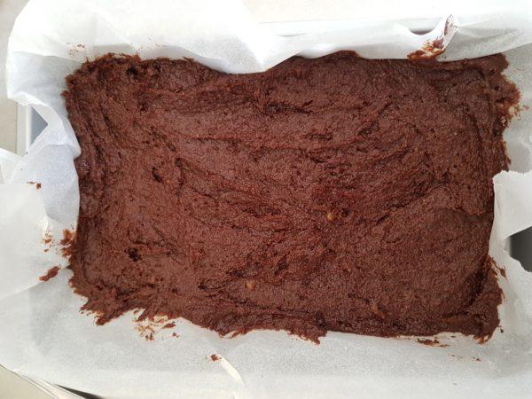 Préchauffez votre four à 180°C. Écrasez la banane à la fourchette dans un grand bol et ajoutez les autres ingrédients principaux les uns après les autres et dans l'ordre en prenant soin de bien mélanger entre temps. Étalez dans un moule à brownie.