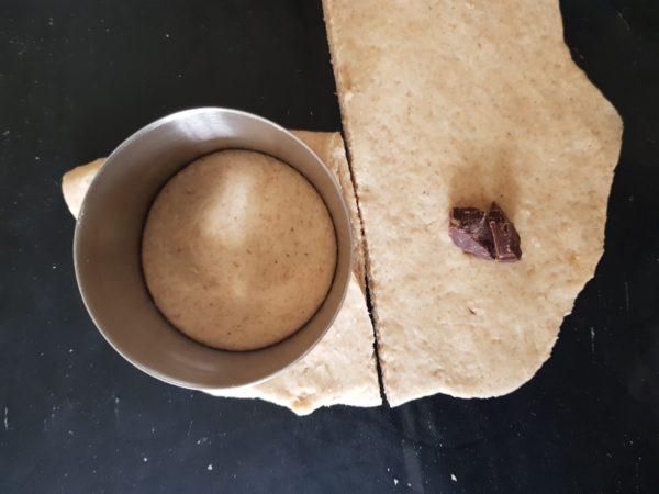 Une fois la pâte bien gonflée, faites chauffer votre poêle à feu doux. Pendant ce temps, dégazer votre pâte et étalez la en l'aplatissant tout d'abord à la main avant de finir au rouleau à pâtisserie. L'épaisseur doit être d'un demi centimètre environ. Faites des rectangles d'environ 16 cm sur 8 avec votre pâte. Repliez-les sur eux-même avant de découper vos beignets avec un emporte-pièce de 5 cm de diamètre, pas plus. Vous pouvez placer des pépites de chocolat, de la purée de cacahuète ou des morceaux de fruits au centre de vos beignets avant de replier la pâte.
